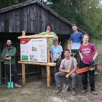 Hier sehen Sie ein Bild von britischen Studenten vor ihrer selbst gebauten Infotafel nahe der Friedrichshütte bei Söllichau