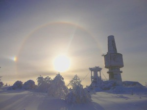 """Aussichtsplattform """"Backöfele"""" und der ehemalige militärisch genutzte Abhörturm auf dem Schneeberg, umgeben von der seltenen Eiscorona am frostigen Winterhimmel."""