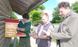 Jan Lippke (Mitte) zeigt sich begeistert vom mobilen Kummerkasten, der an wechselnden Punkten im Naturpark Habichtswald eingesetzt werden kann, um die Meinung der Gäste zu erfragen. Mit im Bild: Uwe Hartmann (links) und Jürgen Depenbrock, Geschäftsführer Zweckverband Naturpark Habichtswald (rechts).