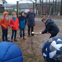 Mit vereinten Kräften wird auf der Schulhofwiese ein Bodenprobennehmer in den Boden geschlagen, um die verschiedenen Schichten des Bodens besser untersuchen zu können (Foto: Naturpark Sauerland Rothaargebirge e.V.).